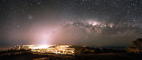 A cold and crisp winters night as the Milky Way rises high above the glow of the capital city, Wellington in New Zealand.