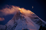 """At 7,821 meters (25,660 feet), Masherbrum is one of the Karakoram Range's most impressive summits. During a trek through the Karakoram atop the Baltoro Glacier, I established camp one night in order to photograph the mountain at sunset. As the new moon rose behind the mountain, a few clouds clung tenaciously to its summit while the prevailing winds blew from the west. Climbers, and photographers too, in fact, pay constant attention to the weather. A sudden change in the jet stream, the prevailing high-altitude wind, could signal an approaching storm. During my trek several storms passed through. In each instance, cameras were appropriately secured and tents assembled in protected locations. A land of glaciers and snow, the Karakorum Range is called the """"the Shining Mountains"""" by the local people, who migrated here from Tibet. Masherbrum stood unconquered by climbers until 1960, when a joint U.S.-Pakistani team achieved the summit. The Baltoro Glacier, which mountaineers follow to reach Masherbrum and other Karakorum peaks, is 93 kilometers (58 miles) long; each day of travel on it reveals new views of high mountains along its edge."""