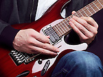 Closeup of man hands playing red electric guitar Ibanez