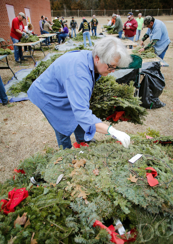 NWA Democrat-Gazette/DAVID GOTTSCHALK  Patti Pando, a volunteer with Bo's Blessings from Kansas, Okla., sorts through a stack of wreaths Friday, February 19, 2016, as she participates in the fourth annual Wreath Recycling Event at the National Guard Armory in Fayetteville. More than 9,000 wreaths collected from the Fayetteville National Cemetery are being broken down for recycling purposes and a bonfire memorial service. All money raised from the event will be donated to the Regional National Cemetery Improvement Corporation for land purchases for the cemetery. Bo's Blessings is a non-profit organization honoring Bo Swearingen, an Army veteran, who died in April of 2010.