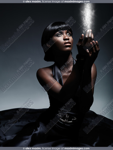 Beautiful young woman wearing long black dress looking at the magical light in her hands