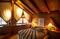 The attic bedroom has a traditional beamed ceiling and a panelled built-in headboard