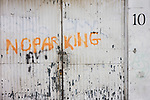 A hand-painted No Parking notice on a garage's gates under railway arches in south London.