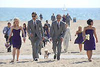 A wedding party walks in the sand after a group photo along the Santa Monica Shoreline on Friday, May 4, 2012.