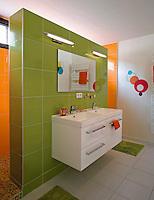 A children's tiled bathroom decorated in acid colours has a double shower concealed behind a partition wall on which a washstand with a double basin is suspended