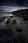 A dark, stormy scene at Newport beach.  It was taken at sunset, creating dark blue clouds and shadows, and has an elongated perspective to capture the line of coastal rocks.