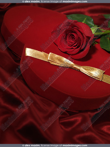 Red heart-shaped gift box and a red rose on red silky cloth