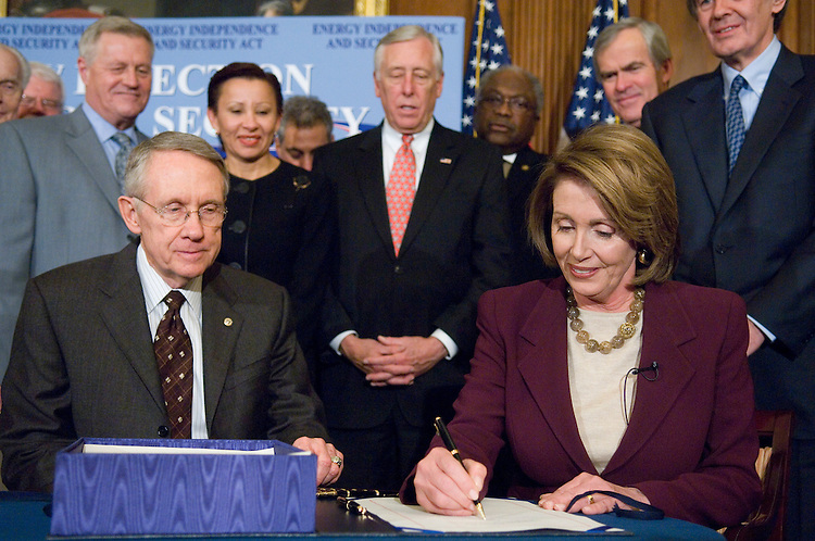 WASHINGTON, DC - Dec. 18: Backed by Senate and House members, Senate Majority Leader Harry Reid, D-Nev., and House Speaker Nancy Pelosi, D-Calif., signing, during an enrollment ceremony for the energy bill, passed by the House earlier Tuesday. Left to right: House Foreign Affairs Chairman Tom Lantos, D-Calif., House Education Chairman George Miller, D-Calif., Rep. Nydia M. Velazquez, D-N.Y., House Democratic Caucus Chairman Rahm Emanuel, D-Ill., House Majority Leader Steny Hoyer, D-Md., House Majority Whip James E. Clyburn, D-S.C., Senate Energy Chairman Jeff Bingaman, D-N.M., and House Select Energy Independence & Global Warming Chairman Edward J. Markey, D-Mass. They sent President Bush a streamlined energy bill that would make the first statutory increase in fuel economy standards in 32 years and require billions more gallons of biofuels to be blended into gasoline over the next 15 years. The president plans to sign the legislation Wednesday, White House spokeswoman Dana Perino said. The bill passed the House by 314-100. (Photo by Scott J. Ferrell/Congressional Quarterly).WASHINGTON, DC - Dec. 18: Backed by Senate and House members, Senate Majority Leader Harry Reid, D-Nev., and House Speaker Nancy Pelosi, D-Calif., signing, during an enrollment ceremony for the energy bill, passed by the House earlier Tuesday. Left to right: House Foreign Affairs Chairman Tom Lantos, D-Calif., House Education Chairman George Miller, D-Calif., House Agriculture Chairman Colin C. Peterson, D-Minn., Rep. Nydia M. Velazquez, D-N.Y., House Majority Leader Steny Hoyer, D-Md., House Majority Whip James E. Clyburn, D-S.C., Senate Energy Chairman Jeff Bingaman, D-N.M., and House Select Energy Independence & Global Warming Chairman Edward J. Markey, D-Mass. They sent President Bush a streamlined energy bill that would make the first statutory increase in fuel economy standards in 32 years and require billions more gallons of biofuels to be blended into gasoline over the next 15 years. The