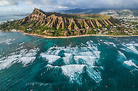 An aerial image of waves rolling towards the shore along the Gold Coast around Diamond Head Crater on a misty day, East O'ahu.