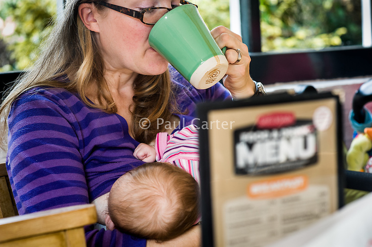 A young woman drinks a cup of coffee while breastfeeding her baby in a cafe with a menu on the table.<br /> <br /> 4 November 2011<br /> Hampshire, England, UK