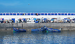 Harbour scene with blue fishing boats, fishermen at work, and seagulls, in Essaouira, Morocco.