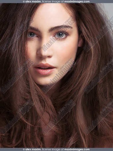 Clsoeup beauty face portrait of a young woman with long brown hair and gray eyes front view