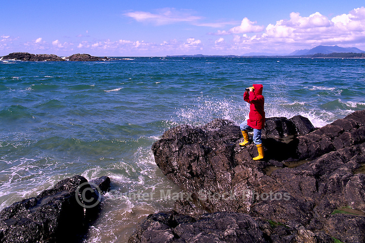 A Person looking through Binoculars and watching for Whales on the Rugged Pacific Coastline near Tofino, on the West Coast of Vancouver Island, British Columbia, Canada (Model Released)
