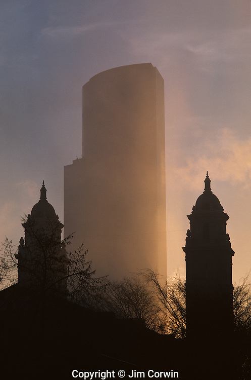 Office building at sunset in fog with Saint James Cathedral Steeples silhouetted downtown Seattle Washington State USA