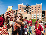 Sarah Pelky, from Tampa, takes a selfie in front of the Unconquered statue at at Doak Campbell Stadium prior to an NCAA college football game between Florida State and Louisville in Tallahassee, Fla., Saturday, Oct. 17, 2015. (AP Photo/Mark Wallheiser)
