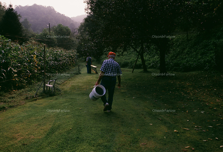 Therman Caudill carries a bucket to gather apples from the last garden he will harvest on his land. He sold his home after a long tired fight with Arch Coal. The family fought the coal company in court to protect their ancestral home which stood in the way of plans to expand a the mine. Caudill, a retired teacher said, said it took only took the mining companies 125 years to force the Caudills out of Mud River--but they finally did it.