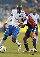 Montreal Impact defender Hassoun Camara (6) dribbles under pressure. In a Major League Soccer (MLS) match, Montreal Impact (white/blue) defeated the New England Revolution (dark blue), 4-2, at Gillette Stadium on September 8, 2013.