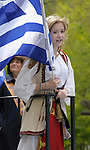 Greek Parade in New York City. A girl in traditional clothes, holds a Greek flag while standing on a float in the Greek Parade in New York City.