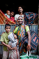 (L-R, back to front) Mohd. Shahin Alom (13, son), Mohd. Abu Taleb (41, husband), Shakil Alom (7, son),  Mahfuza Akhter (5, daughter), Shahida Begum (35). .Shahida Begum, 35, poses for a family portrait in her home in Palashbari Villlage, Taragonj, Rangpur, Bangladesh on 18th September 2011. She contributes to the family income by working as a saleswoman, earning 3500 - 5000 Bangladeshi Taka per month. She is one of many rural Bangladeshi women trained by NGO CARE Bangladesh as part of their project on empowering women in this traditionally patriarchal society. Named 'Aparajitas', which means 'women who never accept defeat', these women are trained to sell products in their villages and others around them from door-to-door, bringing global products from brands such as BATA, Unilever and GDFL to the most remote of villages, and bringing social and financial empowerment to themselves.  Photo by Suzanne Lee for The Guardian