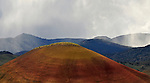 A Painted Hill with approaching rain clouds. Painted Hills, John Day Fossil Beds National Monument. Mitchell, Oregon.