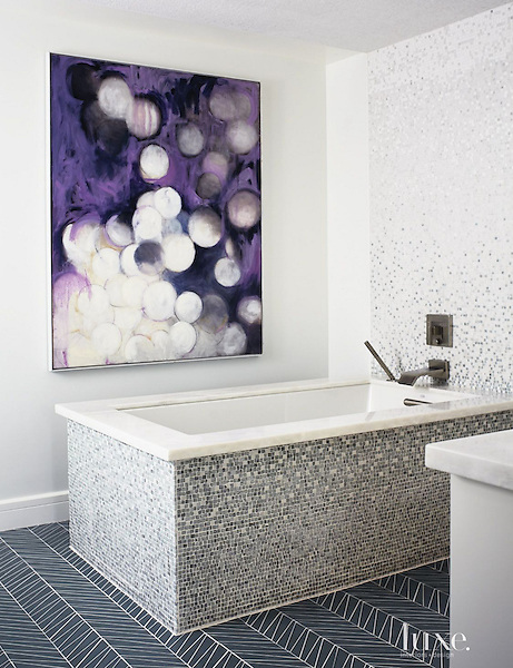 &quot;Tile becomes like artwork in the master bath, where the material, in Mist Mosaic from The Fine Line, wraps a tub from Kohler, as well as a wall backing the faucet, also from Kohler. An abstract painting by Chicago artist Linc Thelen graces another wall.&quot;<br /> <br /> Photography by Laura Moss<br /> <br /> View the full house tour here: luxesource.com/collection/2491/45236<br /> <br /> Visit the Fine Line in Chicago for your next design project: www.finelinetile.com/