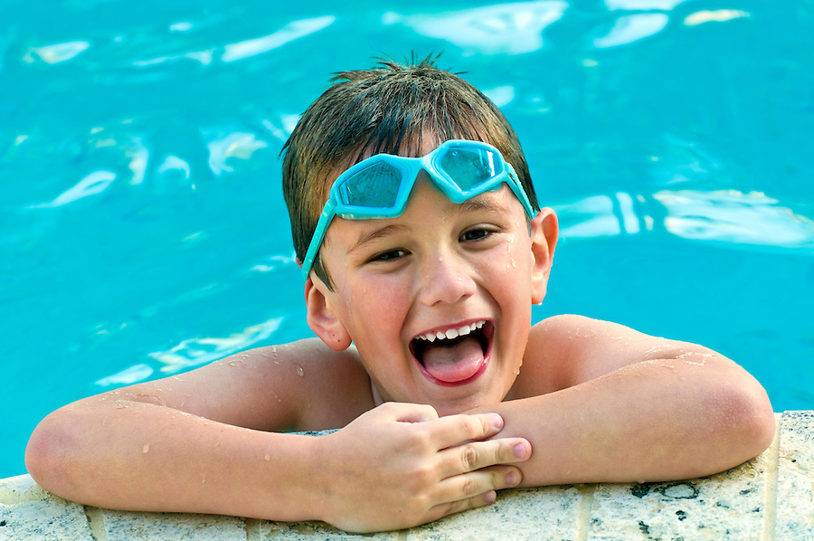 Portrait of a kid laughing in a swimming pool.