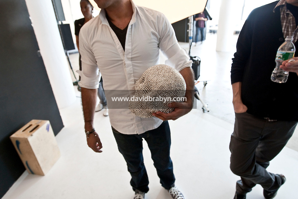 Jeweler-to-the-stars Rodrigo Otazu (C) holds a skull covered in Swarovski crystals during a photo shoot, in New York, 8 November 2009.
