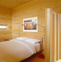 An undulating screen made of wood separates the bed in this wood-clad Scandinavian style bedroom