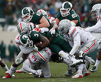Michigan State Spartans running back LJ Scott (3) is taken down by Ohio State Buckeyes linebacker Raekwon McMillan (5) and safety Malik Hooker (24) and linebacker Jerome Baker (17) during Saturday's NCAA Division I football game at Spartan Stadium in East Lansing, Mich., on November 19, 2016. (Barbara J. Perenic/The Columbus Dispatch)