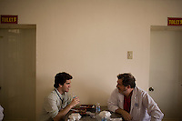 Dr. James Brandt and his son Michael, both from Sacramento, eat lunch together between surgeries at the ORBIS Flying Eye Hospital on Wednesday, April 16, 2008.  Kevin German /  kevin@kevingerman.com..ORBIS Flying Eye Hospital brought doctors, nurses and specialists from all over the world to Ho Chi Minh City, Vietnam from April 7-18, 2008.  The ORBIS program contributed to the efforts of Ho Chi Minh City Eye Hospital in fighting avoidable blindness by educating local ophthalmologists to diagnose and manage pediatric blindness, retinal disease, oculoplastics, and blindness due to glaucoma.