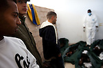 Visitors look at the burnt bodies of nine unidentifiable  soilders tortured by Qadaffi's forces for defecting in Benghazi during the uprising on March 1, 2011.