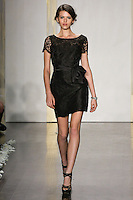 Model walks runway in a black lace pencil skirt dress, bateau neckline, cap sleeves, sash at natural waist bridesmaid dress by Lazaro Perez, from the Noir by Lazaro Spring 2012 Bridal fashion show.