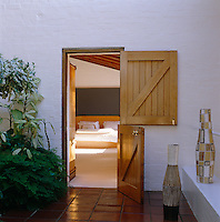 Stable doors open from the contemporary master bedroom on to a terracotta-tiled courtyard