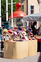 Artisan selling Hand-Crafted Hats at the Public Market at Bastion Square in Victoria, Vancouver Island, British Columbia, Canada (Historic Trial Island Lighthouse Lantern and Fresnel Lens in background)