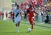Chicago midfielder Patrick Nyarko (14) dribbles down the field while being pursued by LA Galaxy defender Sean Franklin (5).  The LA Galaxy defeated the Chicago Fire 2-0 at Toyota Park in Bridgeview, IL on July 8, 2012.