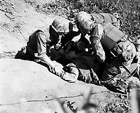 In bitter fighting on Hook Ridge, Marines threw back 800 screaming, bugle-blowing Chinese.  A wounded Marine is given a drink of water by buddies as he lies awaiting evacuation to a rear area aid station.  November 1952.  T.Sgt. Robert Kiser.  (Marine Corps)<br /> Exact Date Shot Unknown<br /> NARA FILE #:  127-N-A166426<br /> WAR &amp; CONFLICT BOOK #:  1447