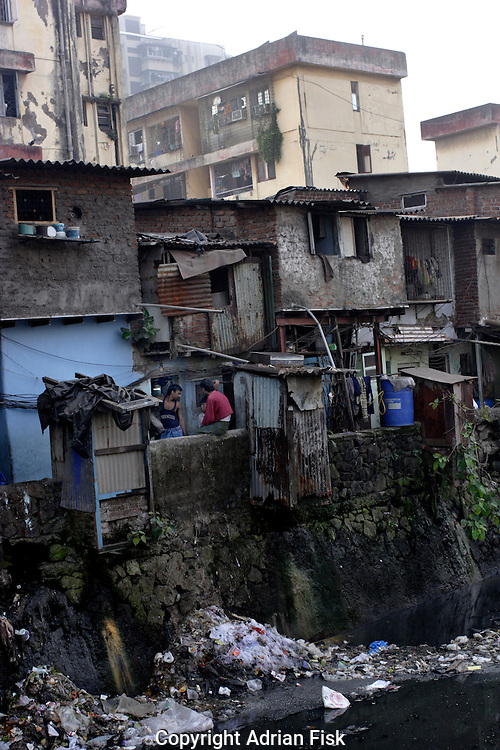 Men talk outside their home in Dharavi on 21st Oct 2006. The water below them acts as the slum drainage and is highly polluted.