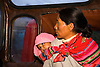 A PERUVIAN WOMAN CARRIES HER BABY ON BUS IN CUZCO