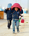 Boys carry buckets and basins on their heads in the Zaatari Refugee Camp, located near Mafraq, Jordan. Opened in July, 2012, the camp holds upwards of 50,000 refugees from the civil war inside Syria, but its numbers are growing. International Orthodox Christian Charities and other members of the ACT Alliance are active in the camp providing essential items and services.