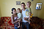 """THIS PHOTO IS AVAILABLE AS A PRINT OR FOR PERSONAL USE. CLICK ON """"ADD TO CART"""" TO SEE PRICING OPTIONS.   Feride Ramadan Mehmed (left) and her husband Mehmed hold their children Birdzhan, 1, and Erdzhan, 3, in their house in the Maxsuda neighborhood of Varna, Bulgaria. They are Turkish-speaking Roma, and were violently driven out of one neighborhood by racist gangs. They took refuge in a United Methodist Church for a year before finding this small house to rent."""