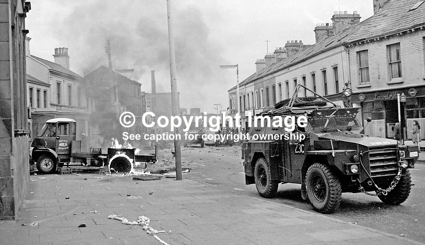 An army personnel carrier patrolling a debris-strewn street passes a burning milk delivery lorry. 197007030251a...The British Army imposed during July 3 &amp; 4, 1970, a 34 hour curfew (except for a two hour break to allow shopping) in approximately 50 streets in the Lower Falls district of Belfast, N Ireland, UK. A military helicopter hovers overhead warning people they would be arrested if they remained on the streets. An army search during the curfew uncovered 100 firearms, 100 home-made bombs, 250 lbs of explosives, 21000 rounds of ammunition and 8 two-way radios. This curfew is often seen as a turning point in souring relations between the Roman Catholic working class and the British Army. The army was no longer seen as the protector of the Catholic community.<br />