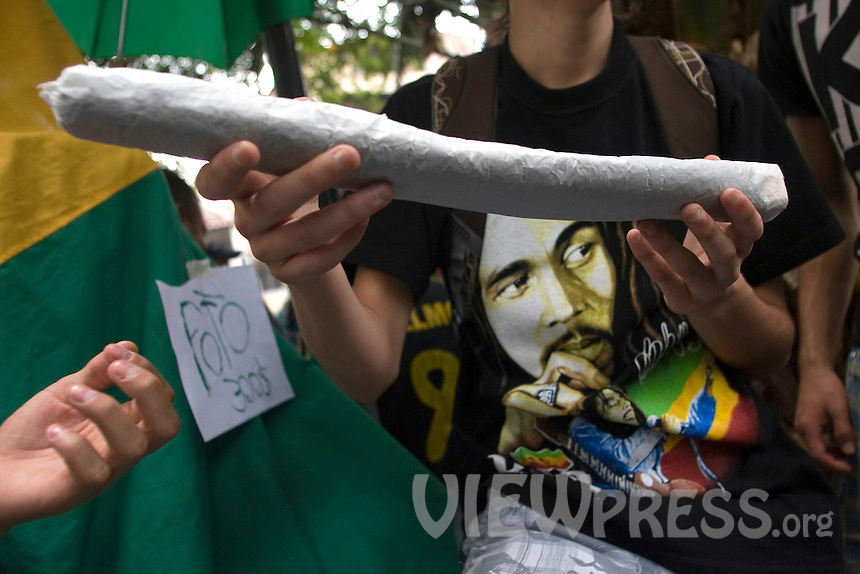 A young man carries a marijuana cigarette on a street during celebrations of the International Day of the Marijuana and for the legalization in Medellin, Colombia, May 5, 2012. Photo by Fredy Amariles/VIEWpress.