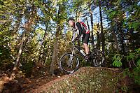 Riding over natural rock features while mountain biking in Copper Harbor Michigan Michigan's Upper Peninsula.