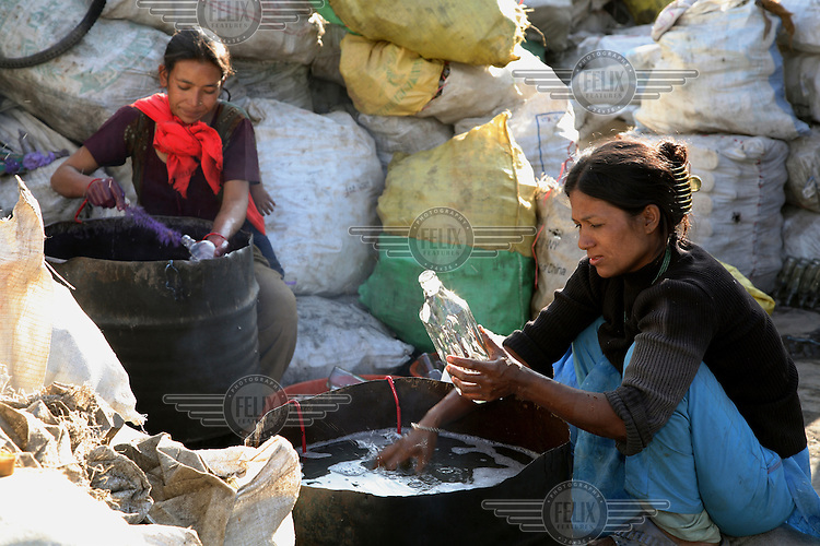 Women washing bottles at a glass recycling centre.