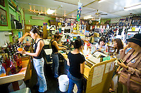 Young women serving Matsumoto's Shave Ice inside their crowded store in Haleiwa on Oahu's North Shore, Hawaii
