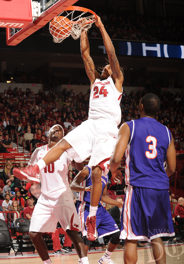 NWA Media/ANDY SHUPE - Arkansas' Michael Qualls dunks over Northwestern State's Devonte Hall (3) during the second half of the Razorbacks' 100-92 win Sunday, Dec. 28, 2014, in Bud Walton Arena in Fayetteville.