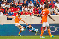 Goalkeeper Ryan Meara (18) of the New York Red Bulls dives for a ball as Brian Ching (25) of the Houston Dynamo passes. The New York Red Bulls defeated the Houston Dynamo 2-0 during a Major League Soccer (MLS) match at Red Bull Arena in Harrison, NJ, on June 30, 2013.