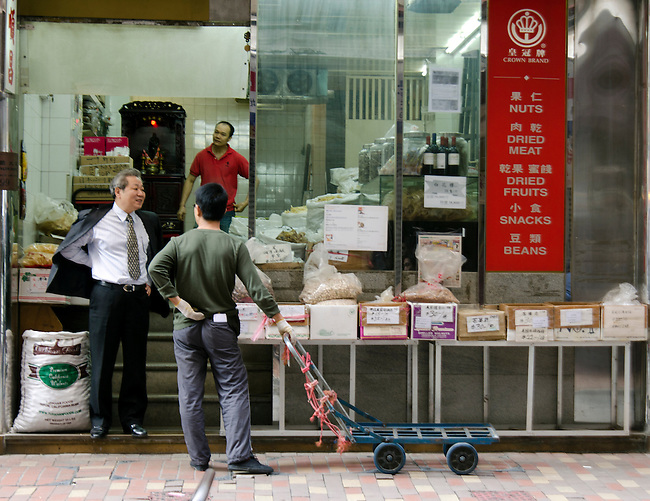 Hong Kong urban scene - men talking in front of store shop