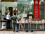 Hong Kong urban scene - men talking in front of store shop