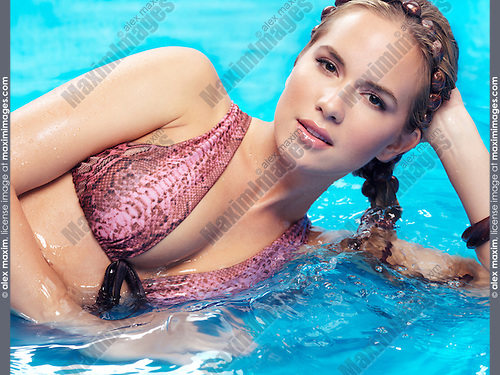 Beauty portrait of a young woman with braided long hair wearing a bikini lying in blue water